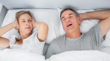 Annoyed wife blocking her ears from noise of husband snoring